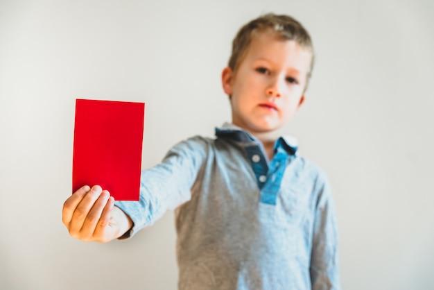 Bambino faccia arrabbiata mostrando un cartellino rosso come un avvertimento, fermare il bullismo concetto, sfondo bianco. Foto Premium