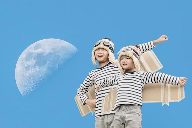Bambino felice che gioca con le ali del giocattolo contro il fondo del cielo di estate. Foto Premium