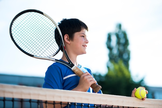 Bambino guardando lontano sul campo da tennis Foto Gratuite