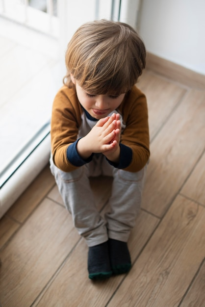 Bambino in giovane età che dice una preghiera a casa Foto Gratuite