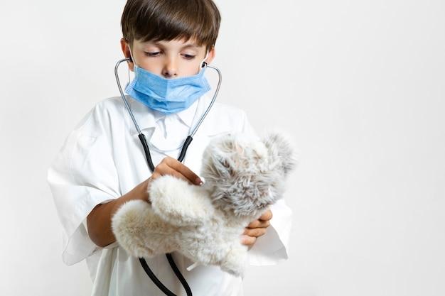 Bambino in giovane età con lo stetoscopio e l'orsacchiotto Foto Gratuite