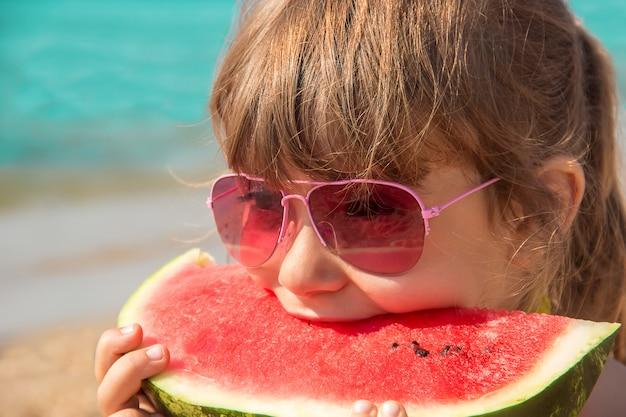 Bambino in mare che mangia un'anguria. Foto Premium