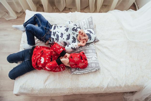 Bambino in morbido pigiama caldo giocando nel letto Foto Premium