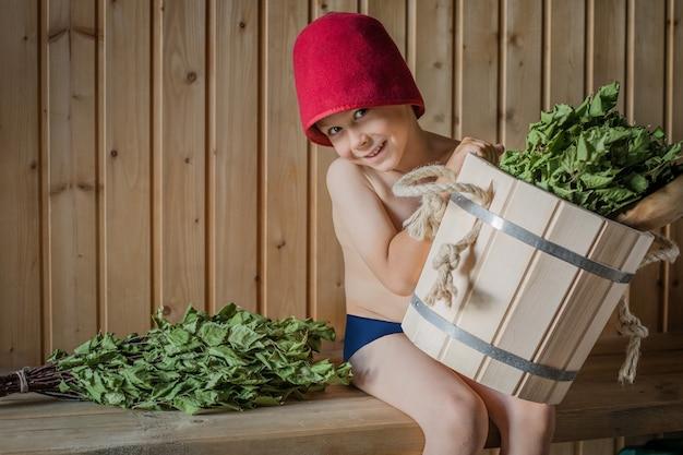 Bambino in un bagno russo con una scopa di betulla Foto Premium