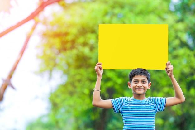 Bambino indiano che tiene manifesto vuoto Foto Premium