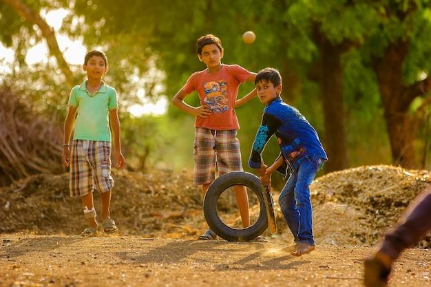 Bambino indiano rurale che gioca cricket su terra Foto Premium