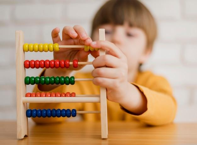 Bambino sfocato che impara a contare usando l'abaco Foto Gratuite