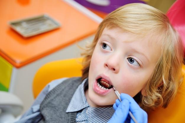 Bambino sorridente con capelli ricci chiari su esame nella sedia dentaria Foto Premium
