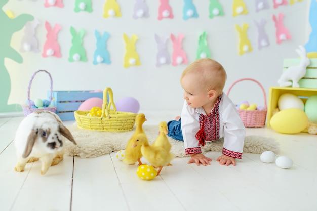 Bambino sorridente sveglio in ricamo tradizionale in decorazioni colorate di pasqua Foto Premium