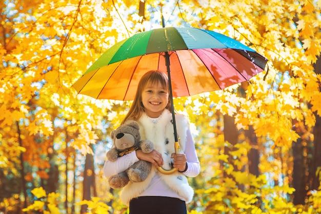 Bambino sotto un ombrello nel parco di autunno. messa a fuoco selettiva. Foto Premium