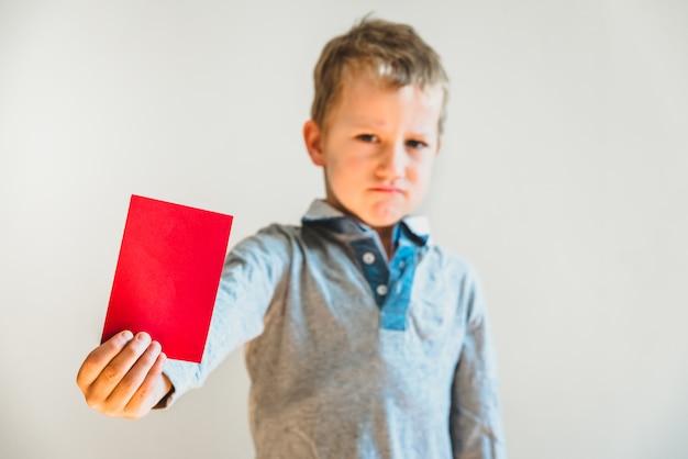 Bambino spaventato con la carta rossa anti bullismo Foto Premium
