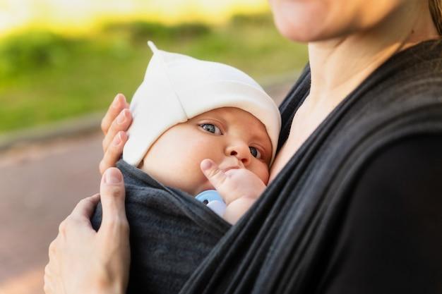Bambino sul seno della madre. il bambino mangia il dito Foto Premium