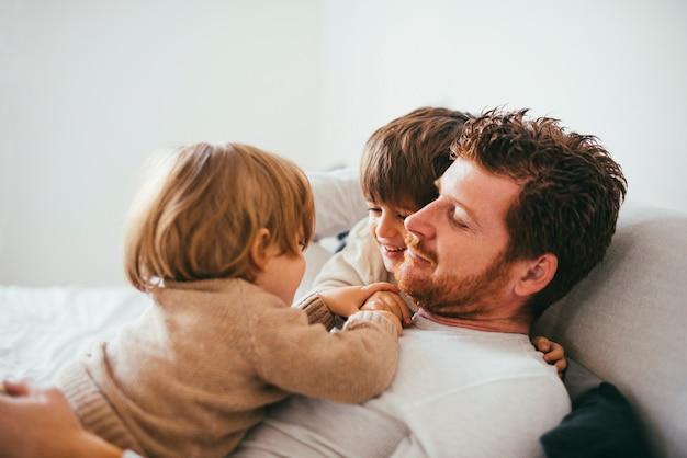 Bambino sulla pancia del padre a casa Foto Gratuite