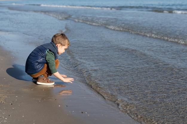 Bambino sulla riva della spiaggia giocando con le onde Foto Premium