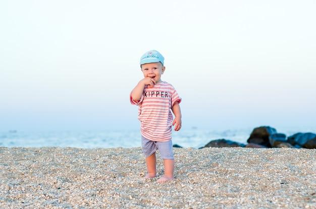 Bambino sulla sabbia vicino al mare in cappello blu e vestiti a strisce. concetto di estate. vacanza rilassante, vacanza al mare. Foto Premium