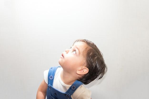 Bambino sveglio del neonato con il pagliaccetto blu su fondo bianco Foto Premium