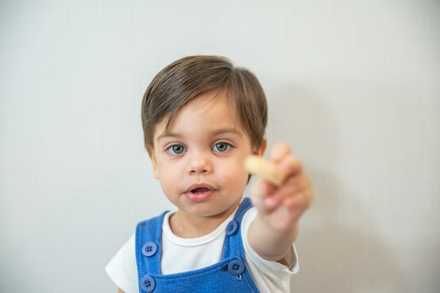 Bambino sveglio del neonato - con pagliaccetto blu su fondo bianco - mangiare wafer Foto Premium