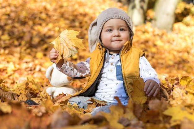 Bambino sveglio di vista laterale che gioca con le foglie Foto Gratuite