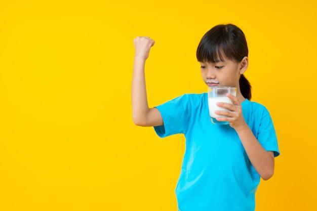 Bambino tailandese felice che tiene il latte alimentare isolato e giovane della ragazza asiatica del bicchiere di latte per forte salute Foto Premium