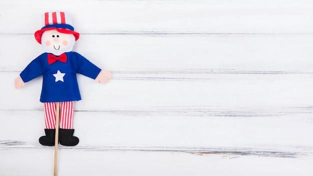 Bambola della bandierina del quarto di luglio su superficie di legno bianca Foto Gratuite