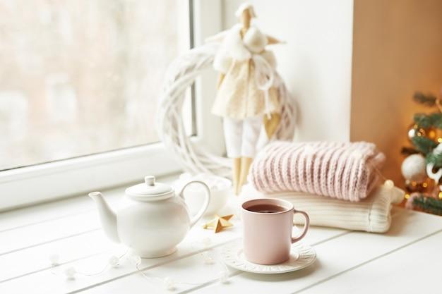 Bambola fatta a mano con set da tè e caramelle gommosa e molle vicino alla finestra. accogliente colazione invernale del mattino. concetto e umore di natale. Foto Premium