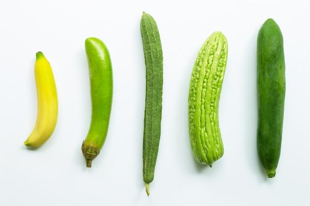 Banana, melanzana lunga verde, luffa acutangula, melone amaro, papaya verde su bianco Foto Premium