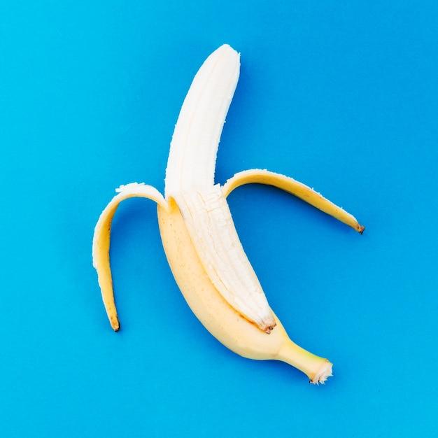 Banana ripulito dalla buccia su una superficie luminosa Foto Gratuite