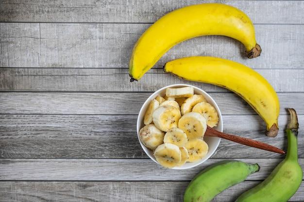 Banane fresche e banane tagliate a pezzi in una ciotola per la salute sul tavolo. Foto Premium