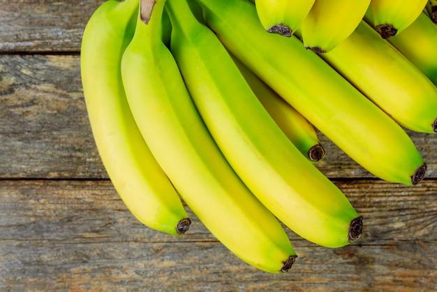 Banane fresche un mazzo su fondo di legno Foto Premium
