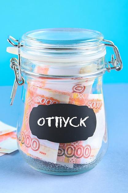 Banca con denaro russo. testo in russo: vacanza. Foto Premium