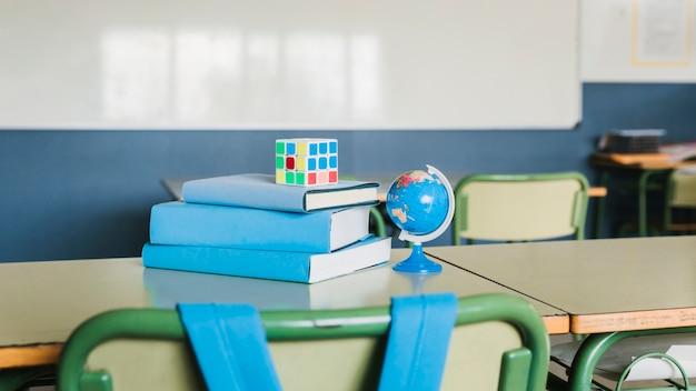 Banco della scuola con libri e cubo di rubik Foto Gratuite