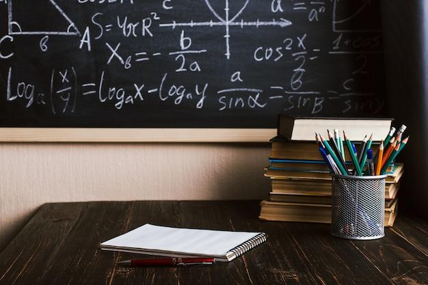 Banco di scuola in aula, con libri sullo sfondo del bordo di gesso con formule scritte Foto Premium