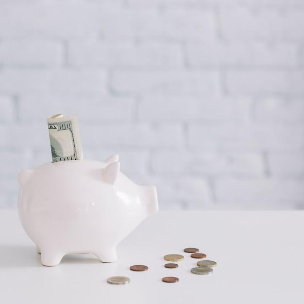 Banconota da cento dollari nello slot piggybank con monete sulla scrivania Foto Gratuite