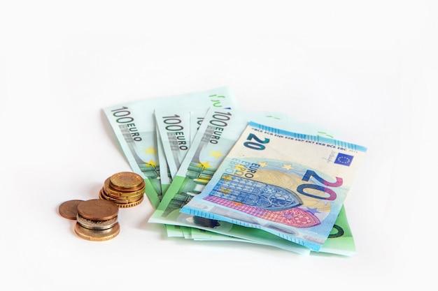 Banconote da 20 e 100 euro e centesimi su uno sfondo bianco isolato. salvataggio. unione europea. Foto Premium