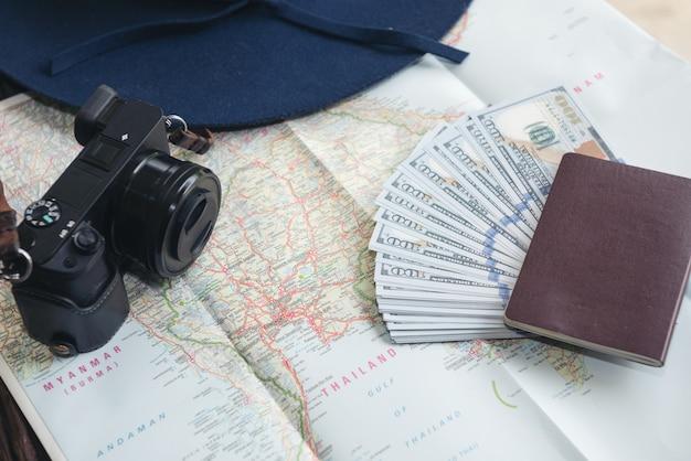 Banconote del dollaro, carta di credito, passaporto, macchina fotografica e cappello blu Foto Gratuite