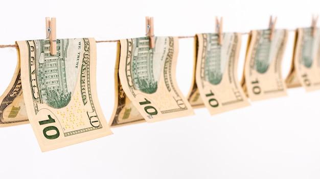 Banconote del dollaro di vista laterale che appendono sulla corda da bucato Foto Gratuite