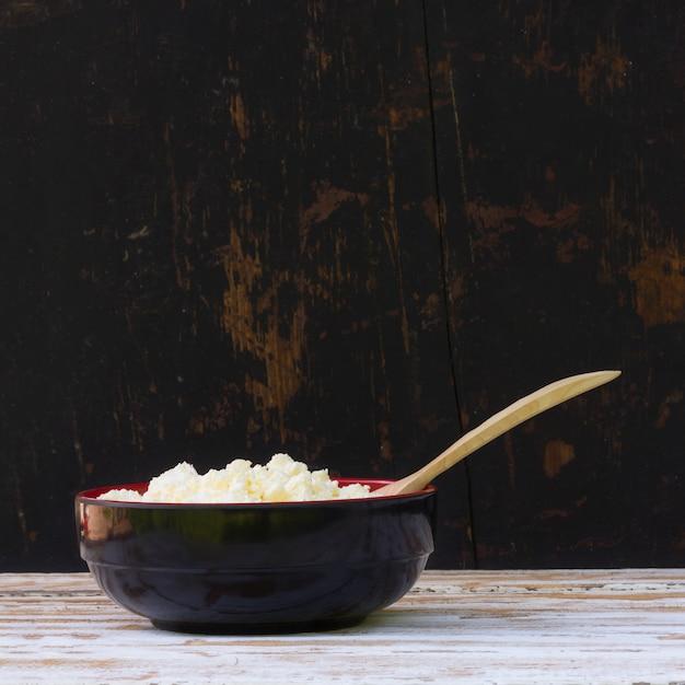 Banda nera con formaggio fresco giallo e ginepro cucchiaio sul tavolo di legno bianco. primo piano vista laterale. Foto Premium