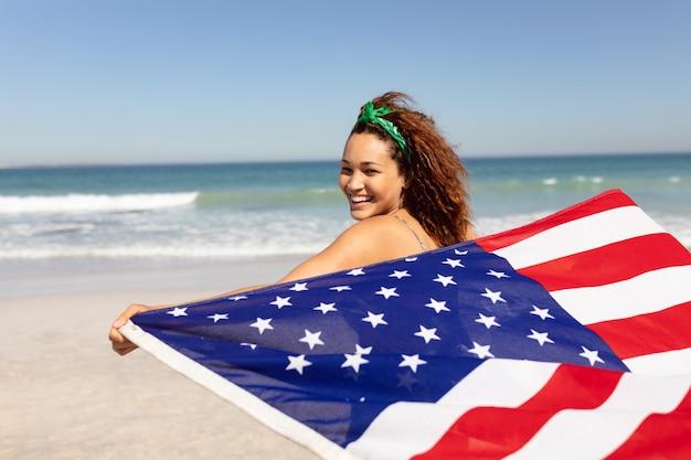 Bandiera americana d'ondeggiamento della bella giovane donna sulla spiaggia al sole Foto Gratuite