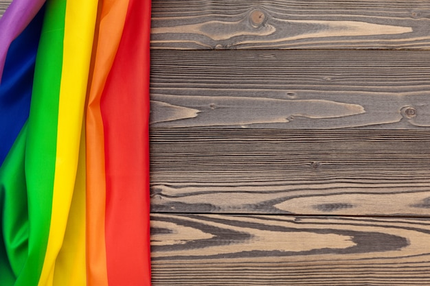 Bandiera del lgbt dell'arcobaleno sul fondo di legno della tavola Foto Premium