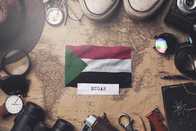 Bandiera del sudan tra gli accessori del viaggiatore sulla vecchia mappa vintage. colpo ambientale Foto Premium