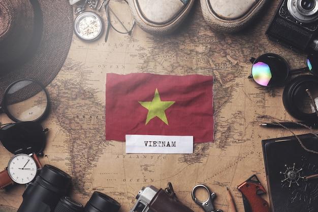 Bandiera del vietnam tra gli accessori del viaggiatore sulla vecchia mappa d'annata. colpo ambientale Foto Premium