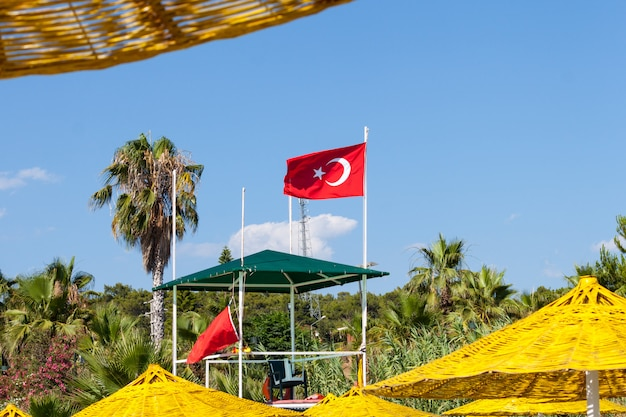 Bandiera della turchia sulla spiaggia. ombrelloni gialli. Foto Premium