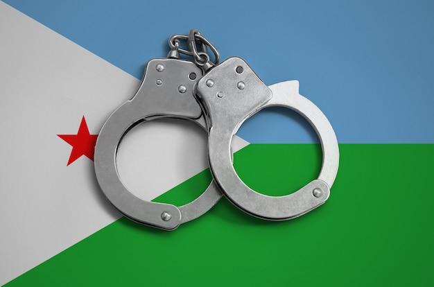 Bandiera di gibuti e manette della polizia. il concetto di osservanza della legge nel paese e protezione dalla criminalità Foto Premium