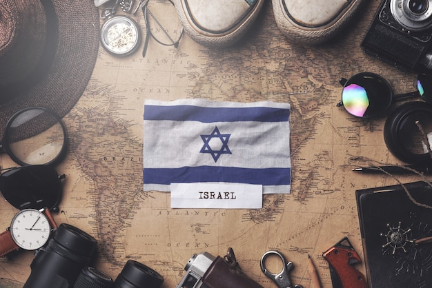 Bandiera di israele tra gli accessori del viaggiatore sulla vecchia mappa vintage. colpo ambientale Foto Premium