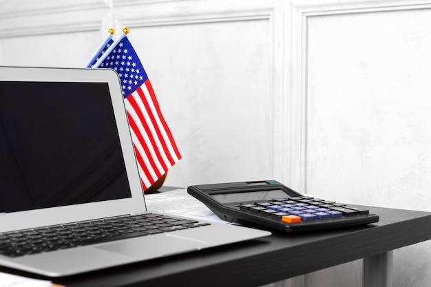 Bandiera e computer portatile degli stati uniti sulla vista superiore della scrivania Foto Premium