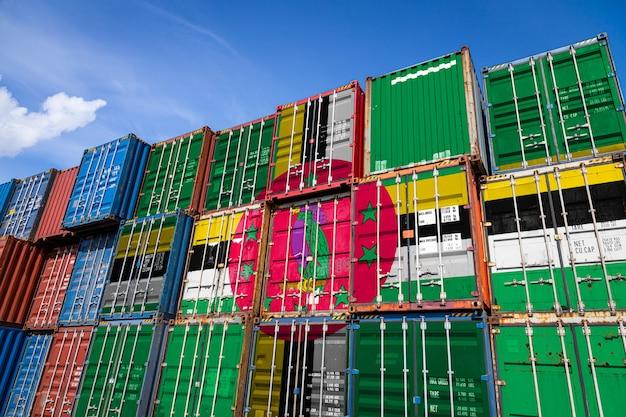 Bandiera nazionale della dominica su un gran numero di contenitori metallici per lo stoccaggio di merci accatastate in file Foto Premium