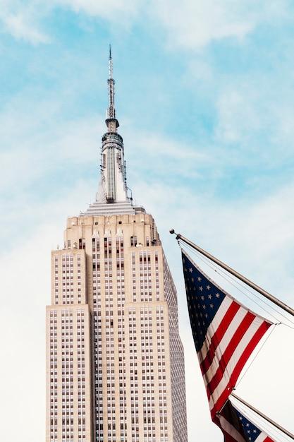 Bandiera usa che fluttua vicino all'empire state building Foto Gratuite