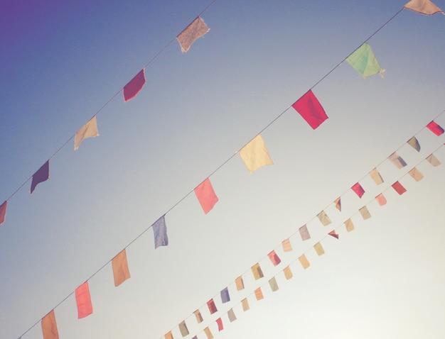 Bandiere colorate su cielo blu con effetto filtro retrò Foto Gratuite