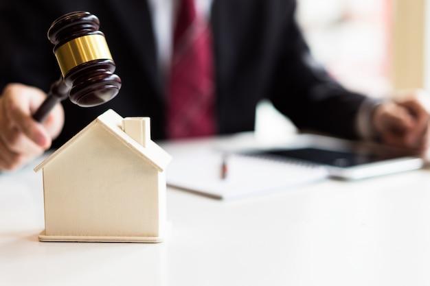 Banditore che abbatte una casa modello con il suo martelletto, asta di vendita di proprietà Foto Premium
