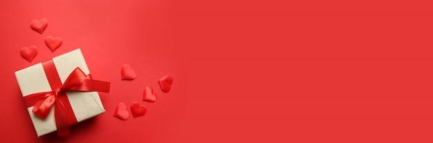 Banner creativo di san valentino. regalo di carta a sorpresa con nastri rossi e coriandoli a forma di cuore rosso su sfondo rosso. concetto di san valentino. vista piana, vista dall'alto, copia spazio Foto Premium